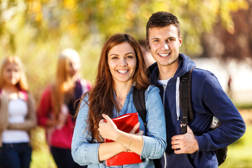 Two happy students in front of the campus
